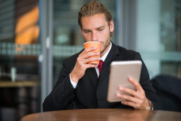 Empresario tomando café mientras revisa correo